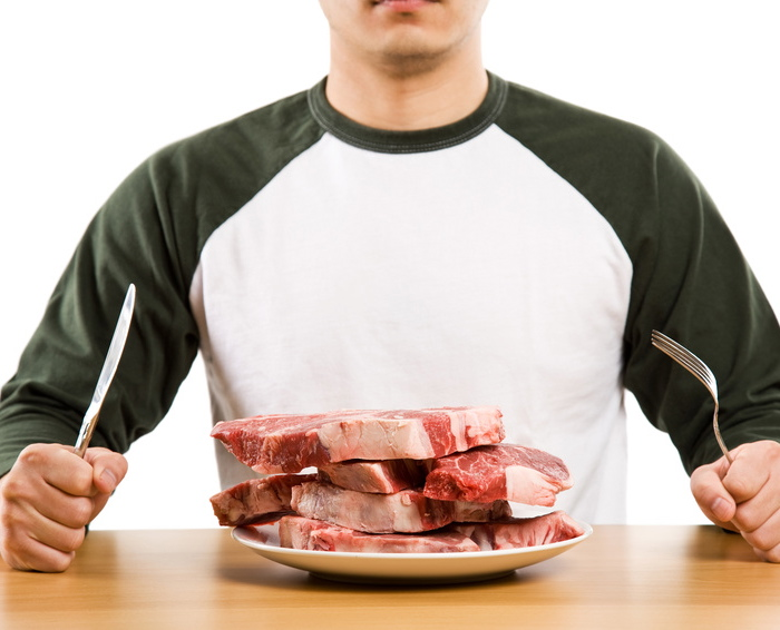 A hungry man holding a knife and a fork ready to eat a stack of raw steak