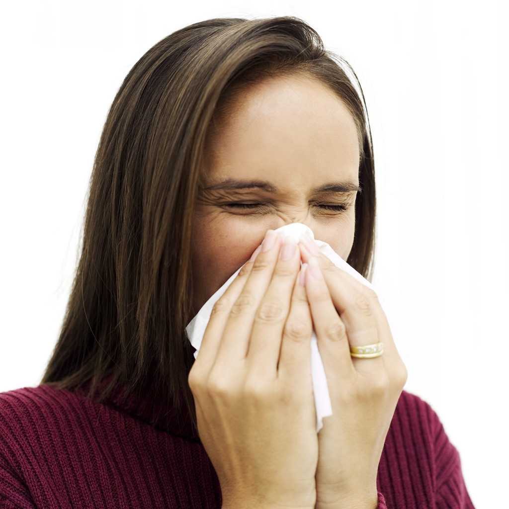 Young Woman Sneezing into a Handkerchief